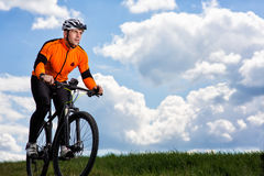 Young man cycling on a rural road through green meadow. Young man cycling on a rural road through green spring meadow during sunset Stock Images