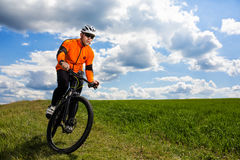 Young man cycling on a rural road through green meadow. Young man cycling on a rural road through green spring meadow during sunset Royalty Free Stock Photos