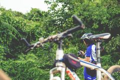 Young man cycling on a rural road and took pictures of nature along the way in the countryside on holiday. Yangon, Myanmar - June 06, 2016 : Young man cycling royalty free stock photo