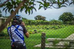 Young man cycling on a rural road and took pictures of nature along the way in the countryside on holiday. Yangon, Myanmar - June 06, 2016 : Young man cycling royalty free stock photos