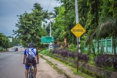 Young man cycling on a rural road and took pictures of nature along the way in the countryside on holiday. Yangon, Myanmar - June 06, 2016 : Young man cycling royalty free stock image