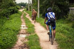 Young man cycling on a rural road and took pictures of nature along the way in the countryside on holiday. Yangon, Myanmar - June 06, 2016 : Young man cycling stock photo