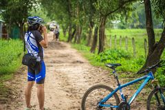 Young man cycling on a rural road and took pictures of nature along the way in the countryside on holiday. Yangon, Myanmar - June 06, 2016 : Young man cycling royalty free stock photography