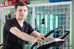 Young man cycling on stationary bike Royalty Free Stock Photography