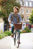 Young Man Cycling Through Urban Park Stock Image