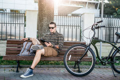 Young Man Cyclist Resting On Bench And Using Tablet Communication Connection Digital Devices Technology Concept. A handsome young man in sunglasses with a Royalty Free Stock Photo