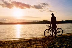 Young man cyclist silhouette on blue sky and sunset above the beach. Biker atthe end of season at lake. Young man cyclist silhouette on blue sky and sunset Royalty Free Stock Photos