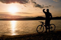 Young man cyclist silhouette on blue sky and sunset above the beach. Biker atthe end of season at lake. Royalty Free Stock Photography