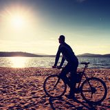 Young man cyclist silhouette on blue sky and sunset background on the beach. End of season at lake. Young man cyclist sit on bike, blue sky and sunset Royalty Free Stock Photos