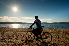 Young man cyclist silhouette on blue sky and sunset background on the beach. End of season at lake. Young man cyclist sit on bike, blue sky and sunset Stock Photos