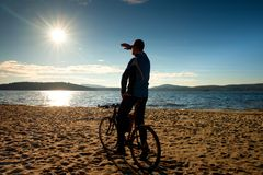 Young man cyclist silhouette on blue sky and sunset background on the beach. End of season at lake. Stock Images
