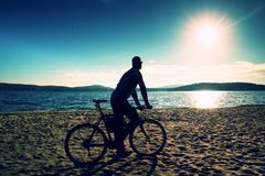 Young man cyclist silhouette on blue sky and sunset background on the beach. End of season at lake. Stock Image