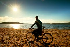 Young man cyclist silhouette on blue sky and sunset background on the beach. End of season at lake. Royalty Free Stock Photos