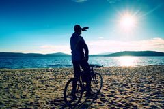 Young man cyclist silhouette on blue sky and sunset background on the beach. End of season at lake. Young man cyclist sit on bike, blue sky and sunset Stock Image