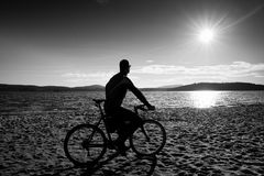 Young man cyclist silhouette on blue sky and sunset background on the beach. End of season at lake. Young man cyclist sit on bike, blue sky and sunset Stock Images
