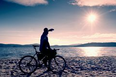 Young man cyclist sit on bike,  blue sky and sunset background on beach. End of season at lake Stock Photos