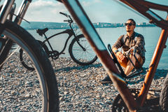 Young Man Cyclist Sits On Seashore And Looking At Sea View. Holiday Travel Activity Concept. Handsome young man cyclist in sunglasses with a backpack sitting on Stock Photos