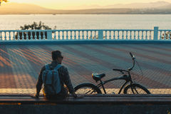 Young Man Cyclist Sitting On The Next To Bicycle Enjoying At The Sunset Vacation Traveling Relaxation Resting Concept. Young man cyclist with a backpack, sits on Royalty Free Stock Photography