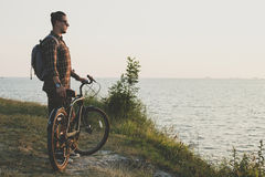 Young Man Cyclist Standing With Bike On Coast And Enjoying View Of Sunset Vacation Traveling Destination Resting Concept Royalty Free Stock Image