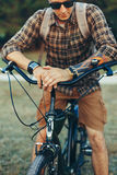 Young Man Cyclist In Sunglasses With Bicycle In Summer Park During Sunset Vacation Traveling Relaxation Resting Concept. A young man cyclist with a backpack, in Stock Photo