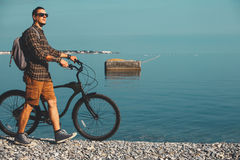 Young Man Cyclist In Sunglasses With Bicycle Walking On Coast And Enjoying View Of Sea. Holiday Travel Activity Concept. Young traveler man with a backpack in Stock Photography