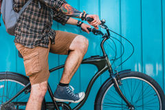 Young Man Cyclist With Tattoo Sitting On Bicycle Near Blue Wall Daily Lifestyle Urban Resting Concept. Unrecognizable young male traveler along a blue wall with stock images