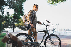 Young man cyclist walks with bicycles on embankment in summer Daily Lifestyle Urban Resting Concept Royalty Free Stock Photography