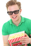 A young man with 3D glasses and a popcorn bucket Stock Photo