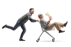 Young man with 3D glasses pushing a shopping cart with a mature Royalty Free Stock Photo