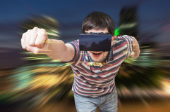 Young man is in 3D simulation of city. He is wearing virtual reality headset Royalty Free Stock Photos
