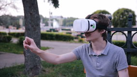 Young man with 3D VR head mounted display in park watching 360 movies, playing VR games.