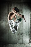 Young man dancer jumping. On wall background royalty free stock photo