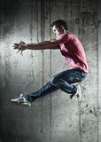Young man dancer jumping. On wall background royalty free stock images