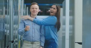 A young man dances in an electronics store and looks at the camera, a woman jumps out and hugs him smiling and laughing. A young man dances in an electronics stock video footage