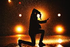 Young man dancing. Young man break dancer dramatic silhouette in club with lights and water Royalty Free Stock Photography