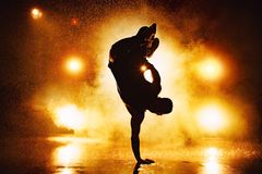 Young man dancing. Young man break dancer dramatic silhouette standing on hand in club with lights and water. Tattoo on body Stock Photo