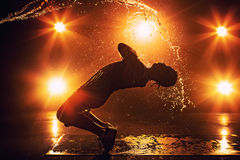 Young man dancing. Young man break dancer with lights and water effects. Tattoo on hand Stock Images