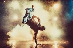 Young man dancing. Young cool man break dancing in club with lights, smoke and water. Tattoo on body Royalty Free Stock Images