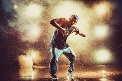 Young man dancing. Young cool man break dancing in club with lights, smoke and water. Tattoo on body Royalty Free Stock Photos