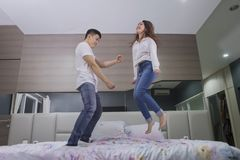 Young man dancing with her wife on the bed stock photo