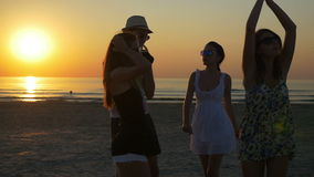 Young man dancing with three female friends on the shore of the ocean. At twilight stock video footage