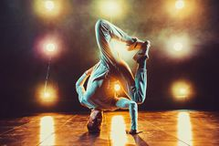 Young man dancing. Young man break dancing in club with lights and smoke. Warm colors Royalty Free Stock Photo
