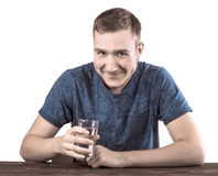 A young man in a dark blue T-shirt is holding a glass of water in his hand,  on a white background. A young male with a glass of water in his hand,  on a white Stock Photo