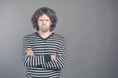 Young man with dark brown hair wears black and white striped casual tshirt looks angry, lips pursed frowning brows, isolated over. Grey background. Keeps arms royalty free stock image