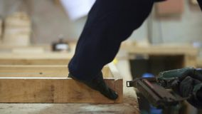 Young man in a furniture factory puts together the wooden pieces for the sofa with a stapler
