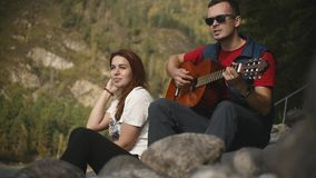 A young man in dark glasses plays the guitar sitting on the rocks by the mountain river of the Altai Republic on a sunny. Day in slow motion stock video