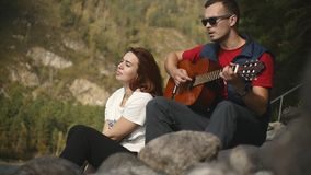 A young man in dark glasses plays the guitar sitting on the rocks by the mountain river of the Altai Republic on a sunny. Day in slow motion stock video footage
