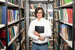 Young man with dark hair standing and holding a black copy book Royalty Free Stock Images