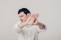 Young man with dark hair in white shirt closed with hands  Royalty Free Stock Photo