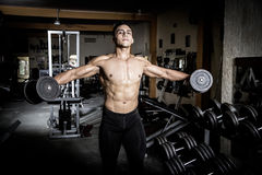 Young man  in dark and old gym Stock Images